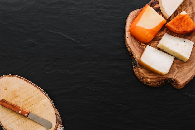 Queijo saboroso e pequena faca na madeira