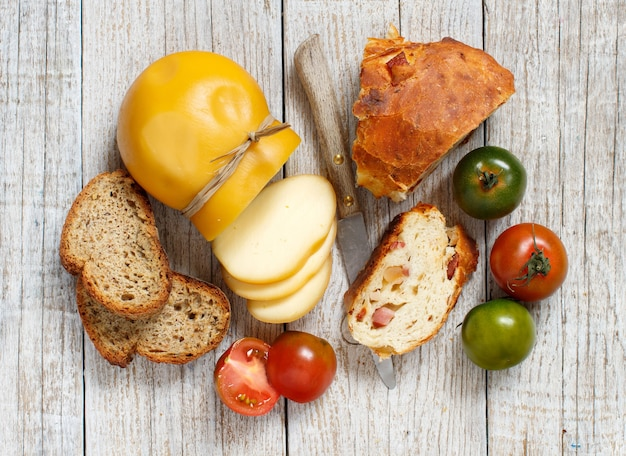 Queijo scamorza, tomate e pão em uma mesa de madeira