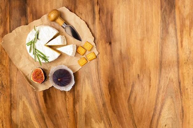 Queijo servido com figos, bolachas e ervas na madeira