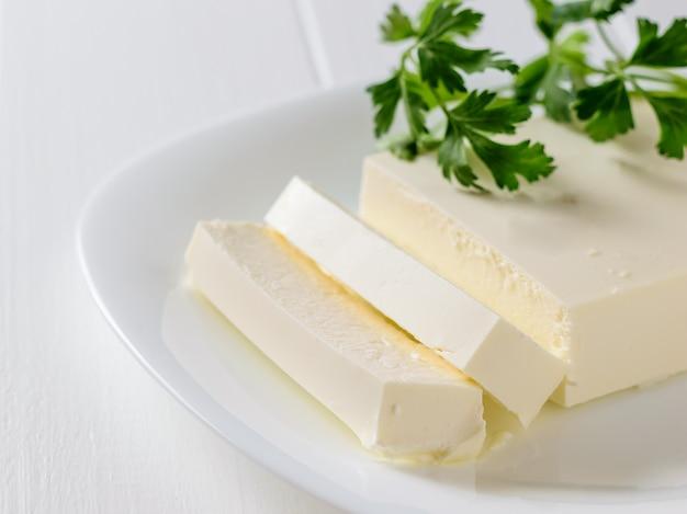Queijo sérvio com salsa em um prato branco sobre uma mesa branca. a vista do topo. produto lácteo.