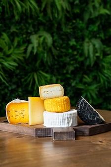 Queijo sortido em uma placa de corte em uma mesa de madeira. fábrica de queijos e loja de queijos. produtos lácteos naturais da fazenda. publicidade e menus.