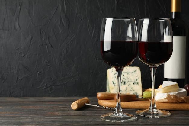 Queijo, uva, garrafa e copos com vinho na madeira