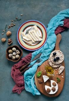 Queijo, uvas e ovos de codorna em fundo de madeira rústico.