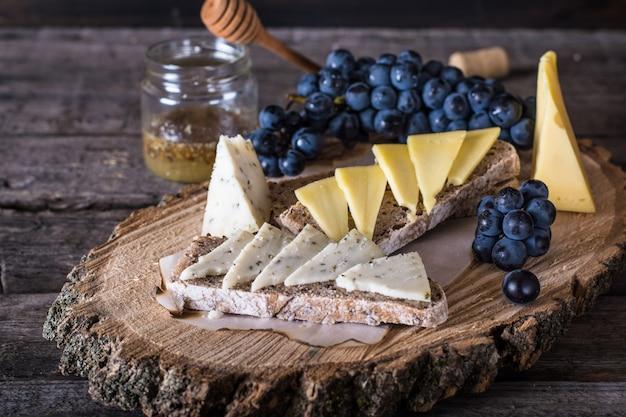 Queijos com uvas, pão, mel. queijo de cabra, ervas. aperitivo. bruschetta com queijo