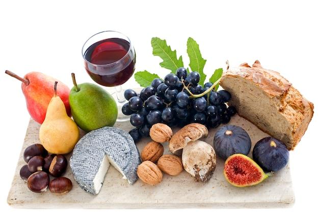 Queijos de cabra, frutas e copo de vinho na placa de madeira, vista superior