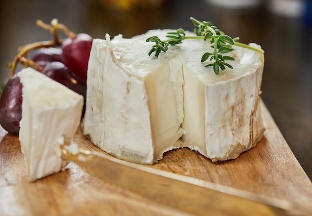 Queijos franceses selecionados com uvas, em tábua de madeira com alecrim e faca.