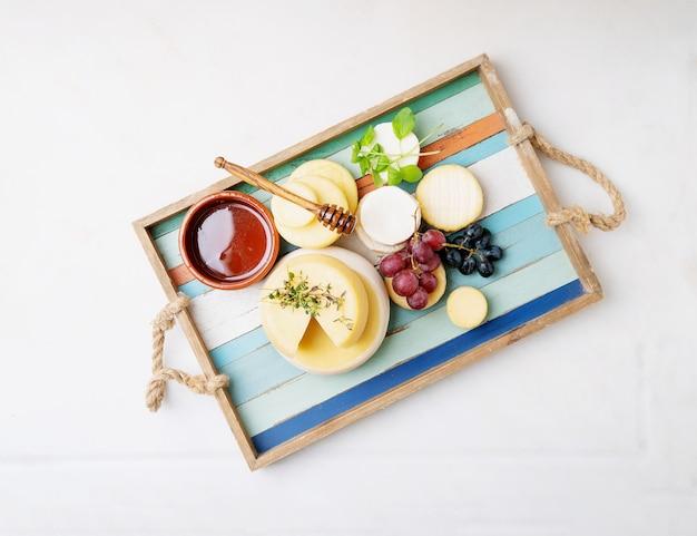 Queijos semi-moles tradicionais portugueses de évora alentejo e açores em tabuleiro, acompanhados de uvas frescas, mel e ervas aromáticas. vista do topo