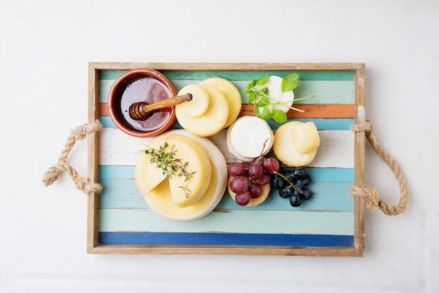 Queijos semi-moles tradicionais portugueses na bandeja, servidos com uvas frescas, mel e ervas. vista do topo