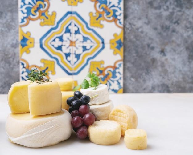 Queijos semi-moles tradicionais portugueses na bandeja, servidos com uvas frescas, mel e ervas. vista lateral. foco seletivo.