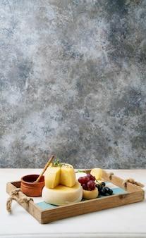 Queijos semi-moles tradicionais portugueses na bandeja, servidos com uvas frescas, mel e ervas. vista lateral