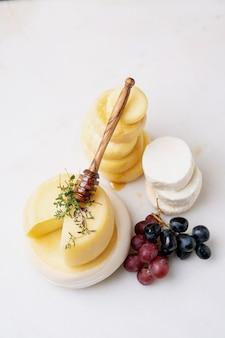 Queijos semi-moles tradicionais portugueses servidos com uvas frescas, mel e ervas. visão de alto ângulo.