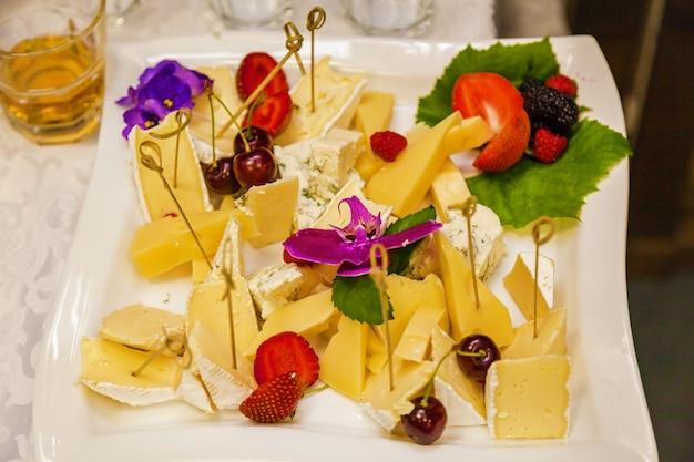 Queijos variados em prato quadrado, pedaços de queijo duro e queijo brie, morangos e cerejas