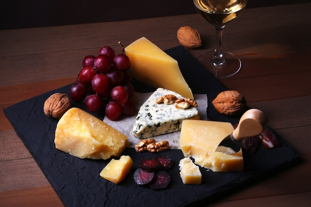 Queijos variados, nozes, uvas, carne defumada e copo de vinho.