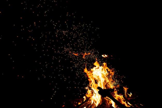 Queima de bosques com faíscas de fogo, chamas e fumaça à noite.