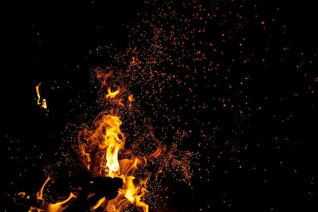 Queima de bosques com fogueiras, chamas e fumaça. figuras impetuosas elementares estranhas estranhas estranhas na noite preta.
