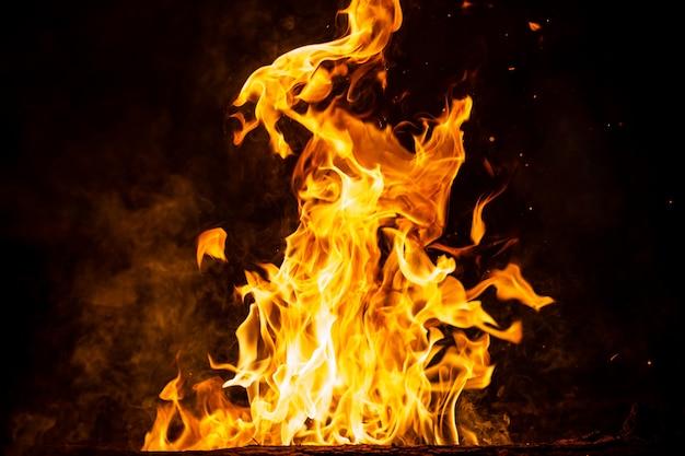 Queima de bosques com fogueiras, chamas e fumaça. figuras impetuosas elementares impares estranhas estranhas no fundo preto. carvão e cinzas. formas abstratas à noite. fogueira ao ar livre na natureza. força do elemento