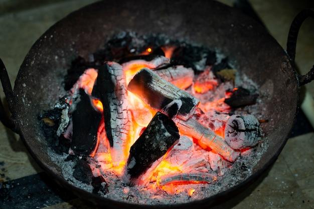 Queima de carvão em um fogão de ferro para aquecimento doméstico. carvão vermelho queimado e cinzas para aquecer a sala.