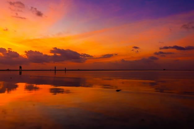 Queima de céu brilhante durante o pôr do sol em uma praia tropical. pôr do sol durante o êxodo, a força das pessoas que andam na água