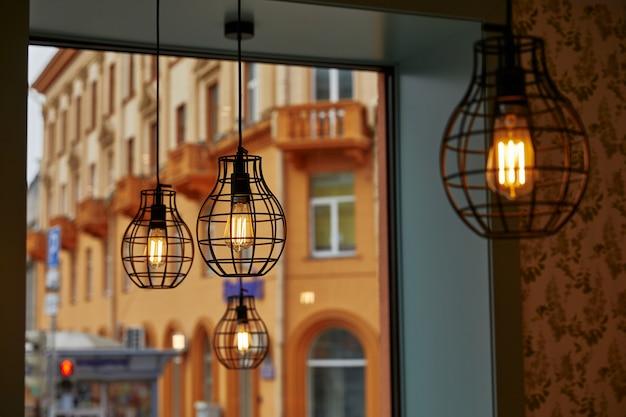 Queima de lâmpadas de forma geométrica contra a janela através da qual a vista dos edifícios