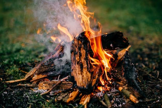 Queima de lenha no acampamento de verão ao ar livre. viagem e turismo. madeira em chamas. brasas e cinzas fumegantes