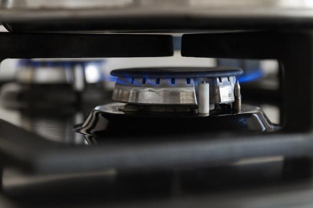 Queima de um fogão a gás de cozinha. chama de gás azul no fogão. closeup, foco seletivo