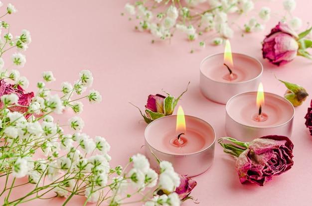 Queima de velas de aroma com flores e rosas secas em rosa. conceito de spa e aromaterapia.