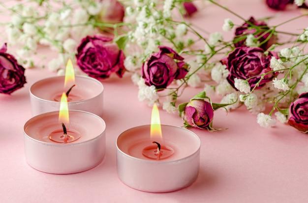 Queima de velas de aroma e rosas secas em rosa. conceito de aromaterapia e romance.