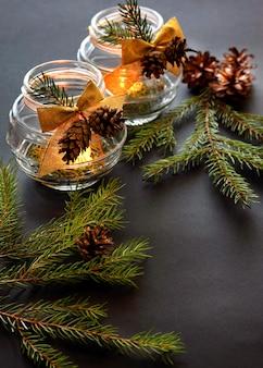Queima de velas de natal em um fundo escuro. ornamentos decorativos.
