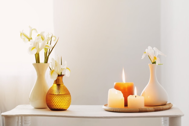 Queima de velas e flores da primavera em uma prateleira de madeira no interior branco