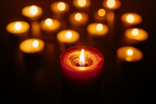 Queima de velas. profundidade superficial de campo. muitas velas acesas à noite. muitas chamas de velas brilhando.