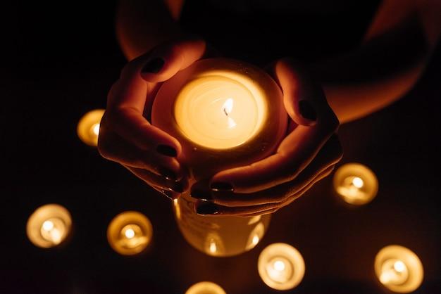 Queima de velas. vela em mãos femininas. muitas velas acesas à noite. muitas chamas de velas brilhando.