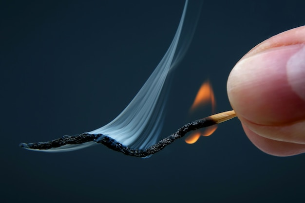 Queimando e fumando fósforo de madeira na mão em fundo escuro. fonte de fogo