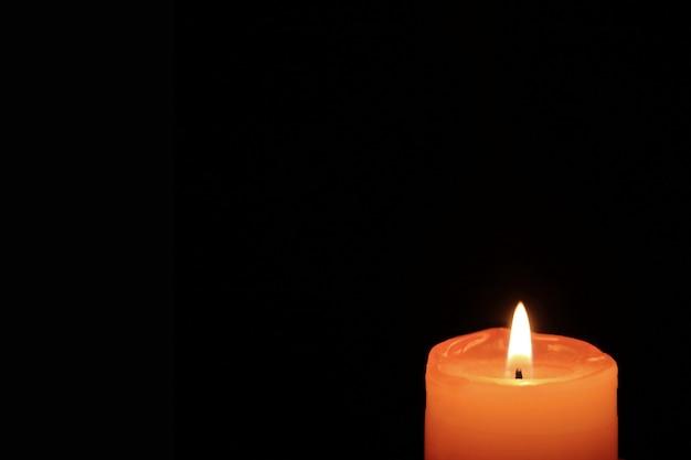 Queimando uma vela de cor laranja em fundo preto