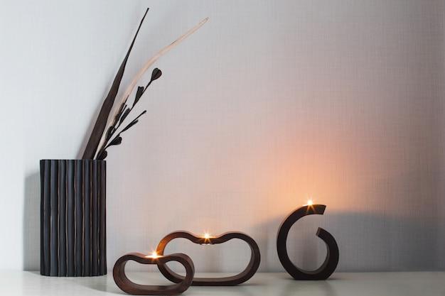 Queimando velas em castiçais de madeira escuros e folhas secas na