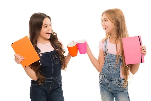 Queixo do queixo. garotinhas na pausa para o chá. crianças pequenas bebendo xícaras juntas no intervalo da refeição. bonitas colegiais aproveitando as férias escolares. temos que fazer uma pausa agora.