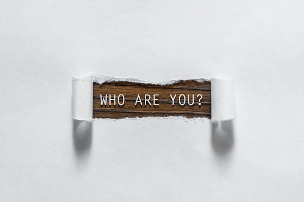 Quem é você pergunta escrita em papel rasgado.