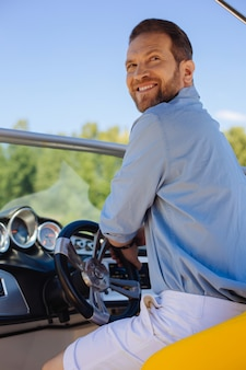 Quem está aqui. jovem encantador sentado atrás do volante de um iate e se virando com um sorriso nos lábios ao ser chamado por alguém