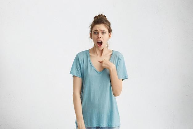 Quem eu? indignada, infeliz, irritada, jovem mulher olhando com expressão questionável como se perguntando: você está falando comigo? realmente? emoções, sentimentos, reações e atitudes humanas negativas