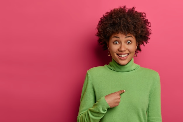 Quem eu? mulher alegre aponta para si mesma e sorri, sendo escolhida ou promovida, não consegue acreditar na sua sorte e escolhida, sente-se elevada e feliz