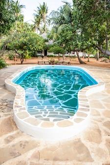 Quênia. piscina luxuosa em jardim africano com cadeiras típicas de madeira no fundo