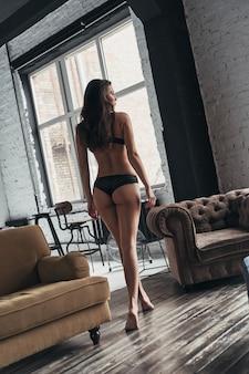 Quente demais para manusear. retrovisor de corpo inteiro de mulher jovem e atraente em roupa íntima, olhando para longe enquanto caminha pela sala em casa