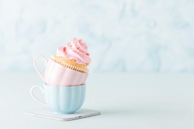 Queque com a decoração de creme cor-de-rosa delicada em dois copos no fundo pastel azul.