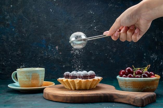 Queque com cerejas ao lado do café com leite e uma mulher peneirando açúcar em pó
