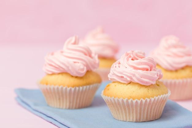 Queque decorado com buttercream cor-de-rosa no fundo do rosa pastel. bolo lindo doce