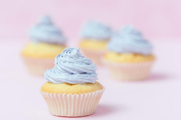 Queque decorado com buttercream violeta no fundo do rosa pastel.