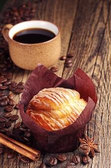 Queque saboroso e xícara de café na mesa de madeira vintage