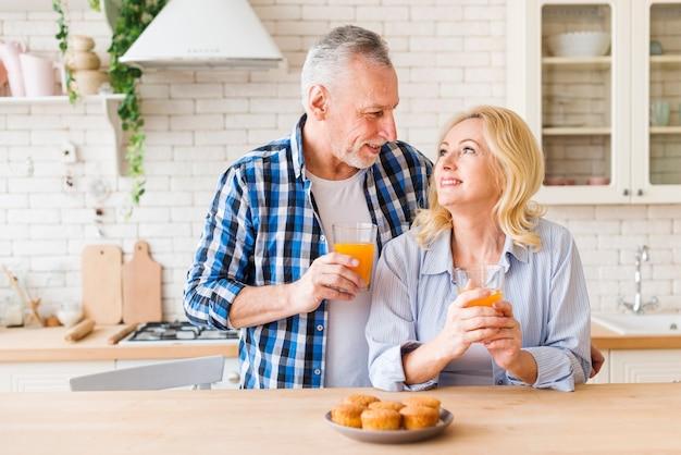 Queques caseiros cozidos na mesa na frente do lindo casal jovem sorridente na cozinha