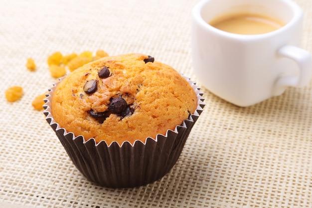 Queques caseiros deliciosos com passas, pedaços de chocolate e café do café no copo branco.