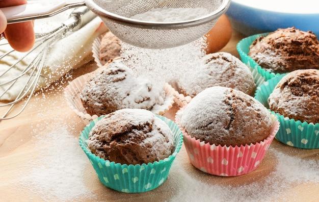 Queques caseiros recém-assados despejando açúcar de confeiteiro na mesa de madeira. bolos caseiros.