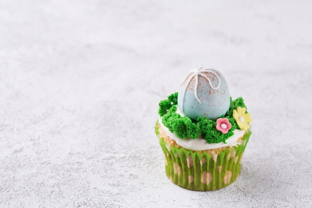 Queques da páscoa com ovos e grama de mástique na tabela. conceito de feriado de páscoa. espaço da cópia